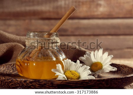 Pot of honey on tray with chamomile on wooden table - stock photo