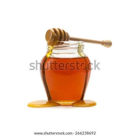 Pot of honey with wooden drizzler on white background - stock photo