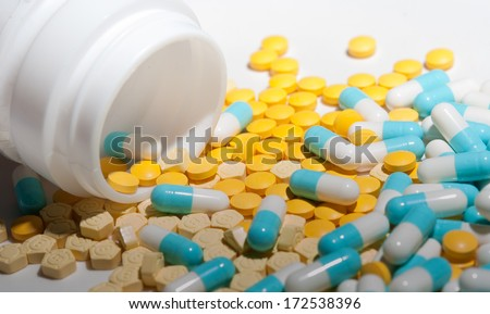 pot of yellow and blue capsule pills - stock photo