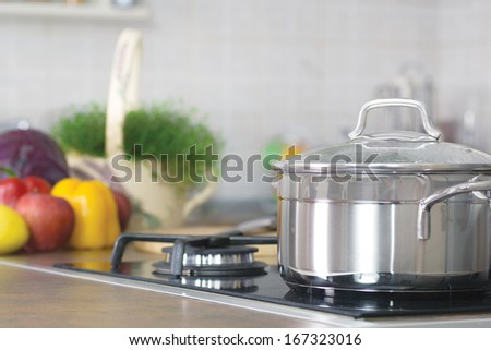 pot on the stove, in the background, fresh vegetables - stock photo