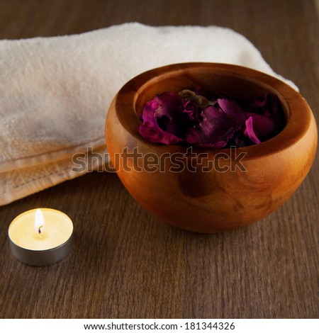 Pot pourri in wooden cup, candle and towel