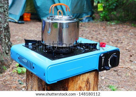 Pot stands on a portable gas slave in tourist camp - stock photo