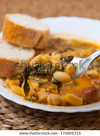 Potaje de Garbanzos y espinacas. Spanish cuisine. Stewed chickpeas with spinach. Image shows a full spoon