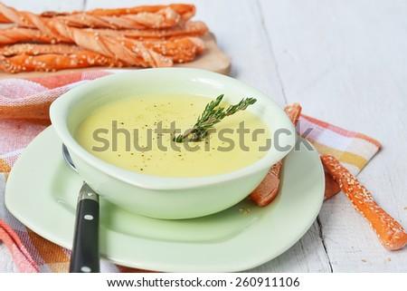 Potato and garlic cream soup with bread sticks - stock photo