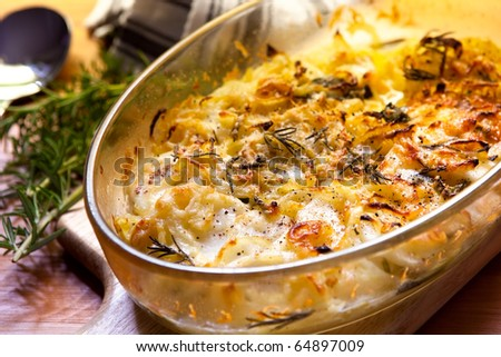 Potato and onion gratin with rosemary, in warm light. - stock photo