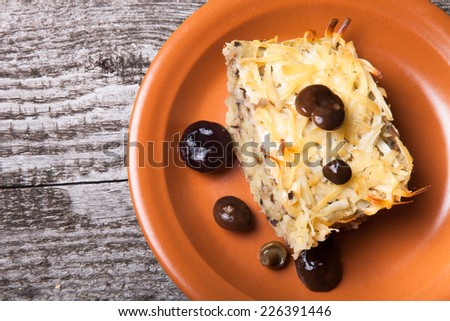 potato casserole with salted mushrooms in a clay plate on old wooden table  - stock photo
