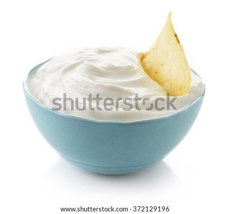 Potato chip in bowl of dip on white background - stock photo