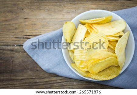 Potato chips bowl isolated on wooden. - stock photo