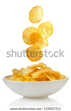 Potato chips falling in a bowl - stock photo