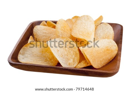 Potato chips from organic products in a wooden plate.