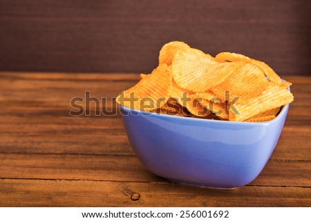 Potato chips in blue plate on background - stock photo
