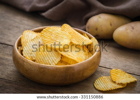 Potato chips in bowl and fresh potato