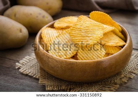 Potato chips in bowl and fresh potato    - stock photo