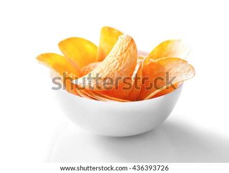 Potato chips in bowl close-up on white background - stock photo
