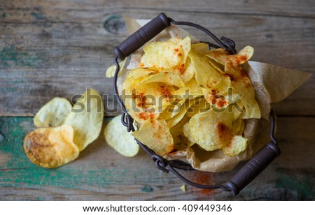 Potato chips in metal basket on a shabby wooden background - stock photo