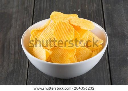 potato chips on wood background - stock photo