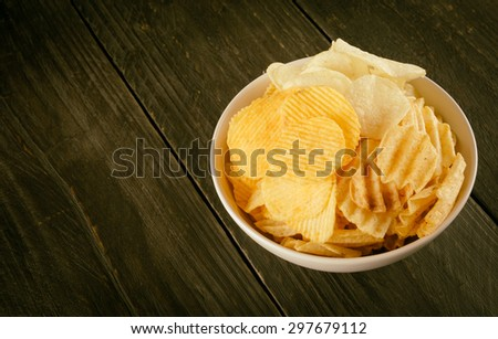 potato chips on wood - soft focus with vintage film filter - stock photo