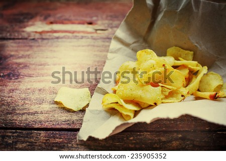 Potato chips over old wooden table.  - stock photo