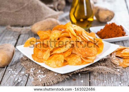 Potato Chips with Paprika Powder on vintage wooden background - stock photo