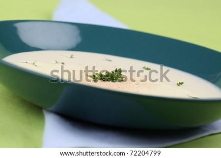 Potato cream soup garnished with cress and freshly grated nutmeg. Shallow dof - stock photo