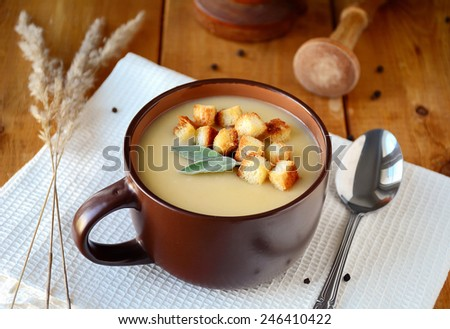 Potato cream soup with croutons garnished with sage leaf in brown soup bowl on wooden table - stock photo