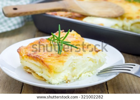 Potato gratin on a white plate - stock photo