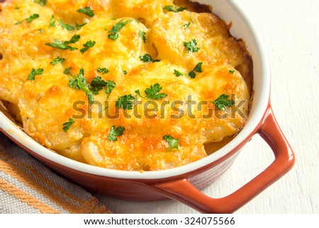 Potato gratin with cream, cheese and parsley in baking dish - stock photo