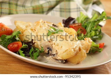 Potato gratin with mushrooms, eggs, cheese and mixed greens - stock photo
