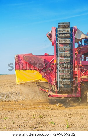 potato harvester in work on field very cllose up  - stock photo