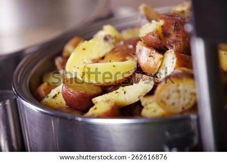 Potato in metal pot - stock photo