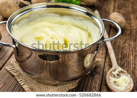 Potato Mash on rustic wooden background (close-up shot)