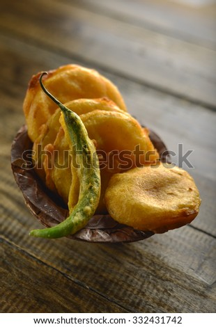 Potato pakora- an indian spicy fritters with fried chili in an eco-friendly bowl. - stock photo