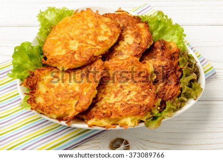 Potato pancakes on white wooden table.