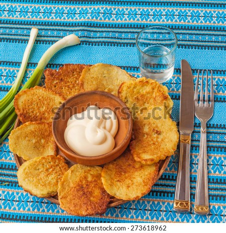 Potato pancakes (potato flapjacks), the traditional Ukrainian cuisine and a glass of vodka on the embroidered tablecloth - stock photo