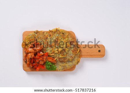 potato pancakes with meat stripes on wooden cutting board