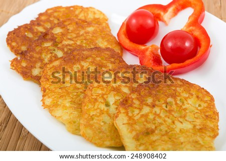 Potato pancakes with vegetables on white plate