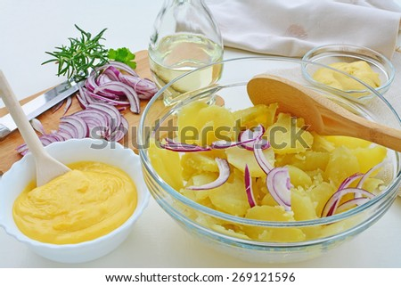 Potato salad with mayonnaise preparation. Boiled potatoes in bowl,  red onions sliced, homemade mayonnaise, oil, mustard and herbs on a white table top. - stock photo