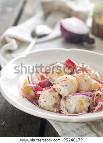 Potato salad with red onion and prosciutto, selective focus