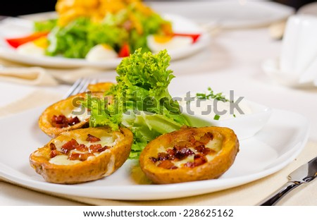 Potato Skins Appetizer with Garnish Served on Plate in Restaurant - stock photo