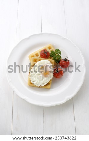 potato waffle with fried egg, grilled tomato and parsley on a white plate - stock photo