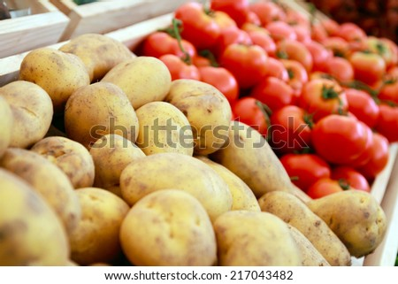 Potatoes and tomatoes in crates - stock photo