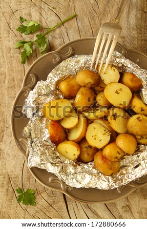 Potatoes baked in foil with herbs - stock photo