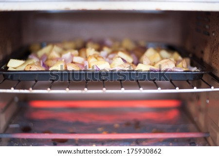 Potatoes baking in toaster oven - stock photo