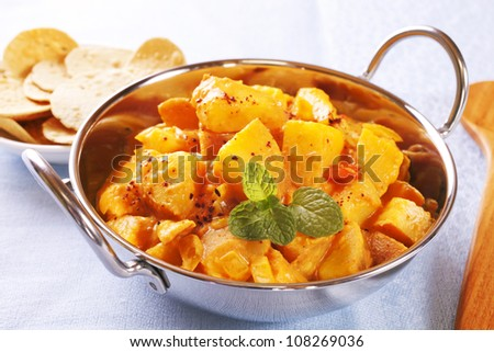 Potatoes cooked in a curry sauce, Bombay Potato is an invention of the Western curry houses. - stock photo