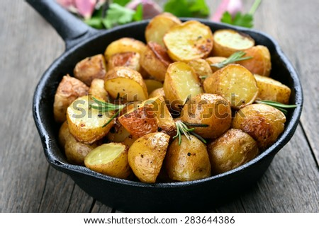 Potatoes fried in pan on rustic table, close up view - stock photo