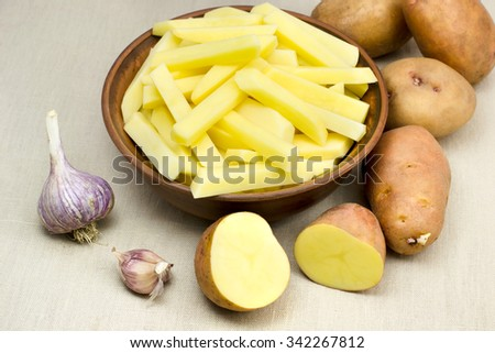 potatoes in a clay dish and garlic - stock photo