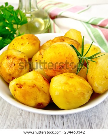 Potatoes roasted with rosemary in a white plate, napkin, parsley, vegetable oil on a background of pale wooden plank - stock photo