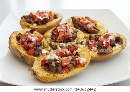 Potatoes stuffed with meat, vegetables and sour cream - stock photo