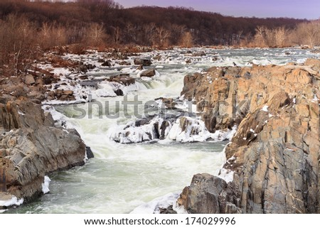 Potomac River and snow-capped rocks in winter at Great Falls National Park in Virginia. - stock photo