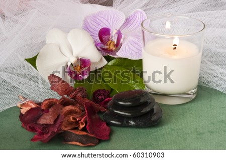 potpourri  with a lighted candle and orchid on green background